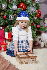Little girl with a gift in Christmas tree