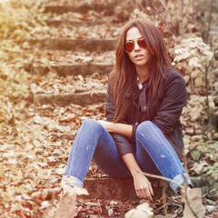 Outdoor fashion portrait of young sexy woman in jeans, jacket an