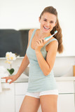 Fototapety Happy young woman with electric toothbrush in bathroom