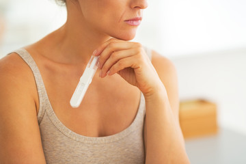 Closeup on young woman with pregnancy test