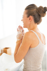 Happy young woman washing hands in bathroom