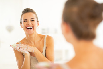Portrait of happy young woman washing hands in bathroom