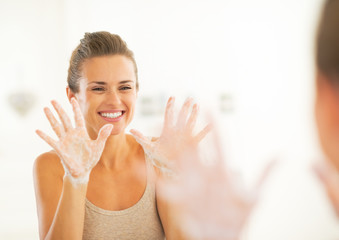 Happy young woman showing soapy hands