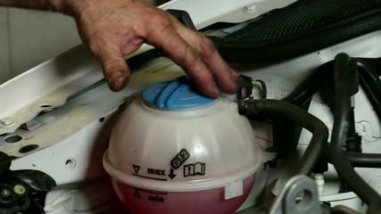 Car Repair Mechanic Places the Refrigerant Circuit Cap