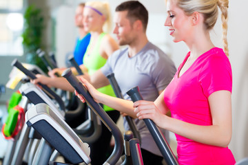 Men and women on treadmill in gym