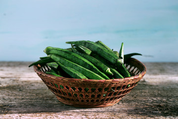 Okra or bhindi, bamia stacked in a basket on wood background