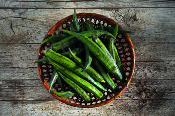 Okra or bhindi, bamia vegetable in a basket on wood background