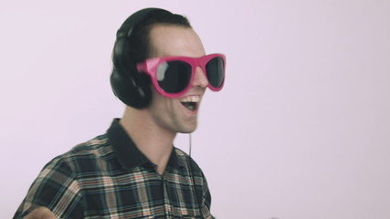 Young man dancing with funny big glasses and headphones