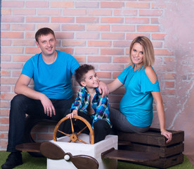 family on the brick wall background in blue clothes