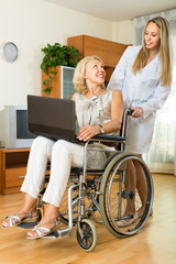 Social worker and invalid with laptop