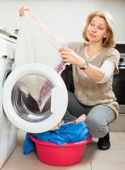 Unhappy woman cheking white clothes near washing machine