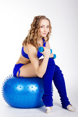 Young woman is sitting on the fit-ball