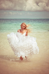 young beautiful woman in dress of bride runs on waves of sea