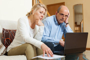 Serious mature couple  with laptop