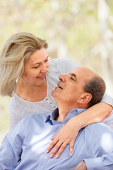 Smiling aged man and woman hugging each other