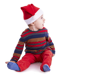 Baby boy with a Santa cap looking amazed to the right