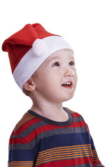 Baby boy with a Santa cap looking amazed upwards
