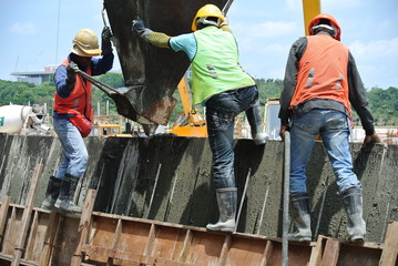 Group of construction workers casting retaining wall