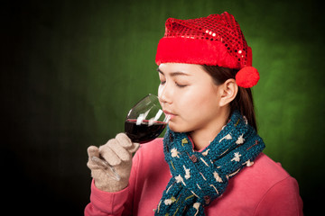 Asian girl with red christmas hat drink red wine