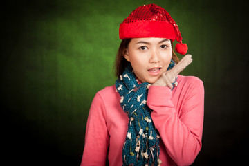 Asian girl with red christmas hat surprised