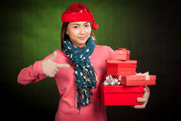 Asian girl with red christmas hat point to gift boxes