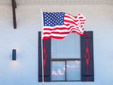 American Flag Reflecting in the Window of a Storefront - 72283316