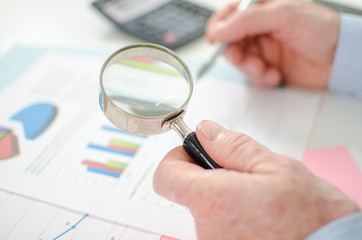 Businessman checking a graph with a magnifying glass