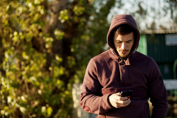 Portrait Of Man In Hoodie Holding Mobile Phone