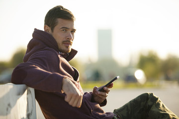 Attractive Man In Hoodie Holding Mobile Phone Texting Outdoor