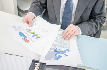 Businessman checking a file with financial graphs