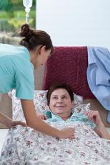 Bedridden woman and helpful nurse
