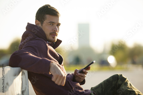 Attractive Man In Hoodie Holding Mobile Phone Texting Outdoor - 72284506