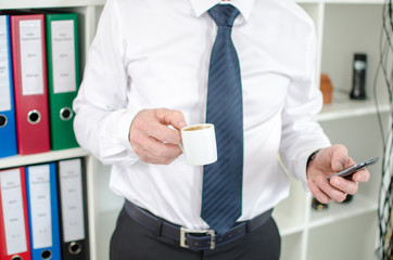 Businessman holding a cup of coffee and a smartphone