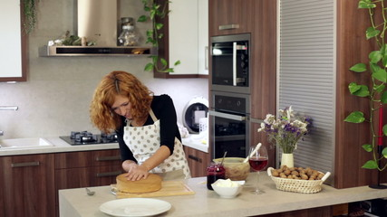 Young happy woman cutting homemade cake in kitchen at home.
