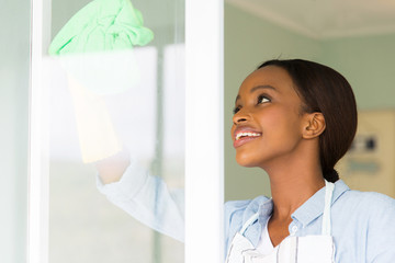 african woman cleaning window glass