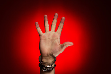 hand in handcuffs over red background