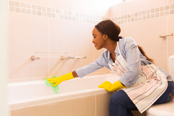 young african housewife cleaning up bathtub