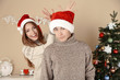 Nice love couple near Christmas tree. Woman and man celebrating