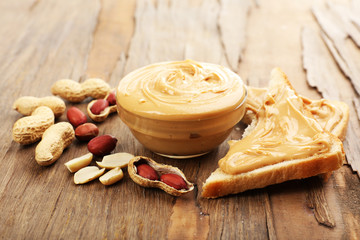 Creamy peanut butter in bowl on wooden table, close-up
