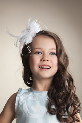 Portrait of elegant little girl posing in studio