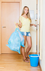 woman staying at the door with trash bags