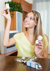 Smiling woman holding light bulbs