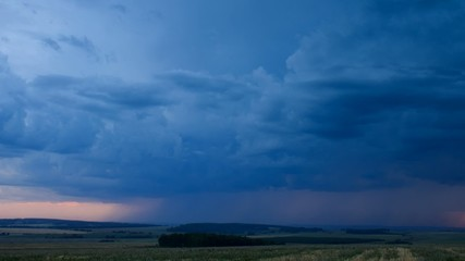 Storm dark clouds over field an sunset, time lapse full HD.