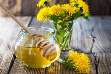 Flower honey in a glass jar and dandelions