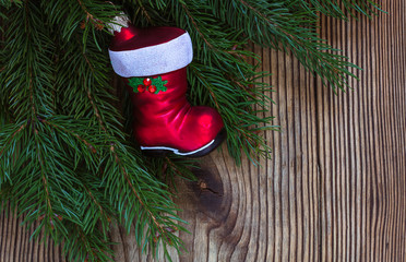 Christmas background with a pine branch and red Santa Claus boot
