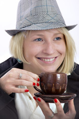 Smiling young woman with a hat and a clay cup