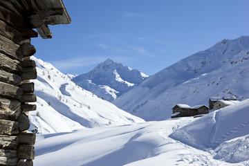 Tief verschneite Landschaft mit alten Häusern und blauem Himmel