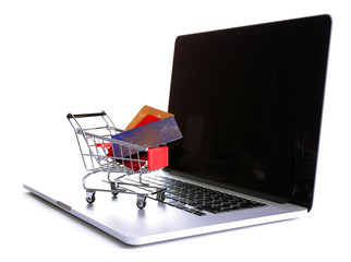 Shopping cart  with credit cards on laptop isolated on white