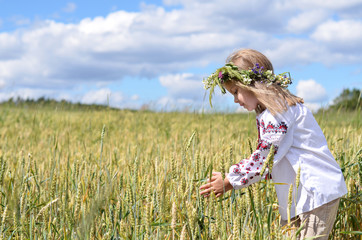Young girl with wreath holding wheat ears on the field