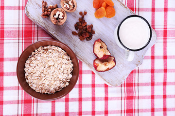 Bowl of oatmeal, mug of yogurt, marmalade, chocolate, raisins,